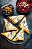 Filo pastry triangles with beetroot cream and olives