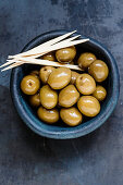 Preserved green olives with toothpicks