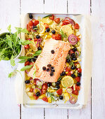 Mediterranean salmon on a baking tray with olives and tomatoes