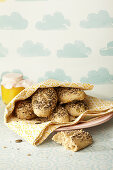 Homemade seeded rolls in a tea towel