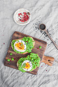 Toasts with mashed green peas and boiled egg, served with pink pepper and black sesame