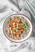 Easy miso soup with soba noodles and fried tofu, sprinkled with chopped spring onion and black sesame seeds