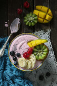 A smoothie bowl with raspberry yoghurt, fresh fruit and poppy seeds