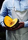Cut open pumpkin being held by a farmer