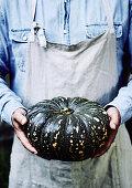 Whole pumpkin in farmers hands