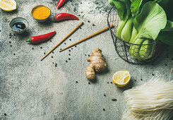 Asian cuisine ingredients over grey concrete background, copy space, vegetables, spices, noodles, sauces for cooking vietnamese, thai or chinese food