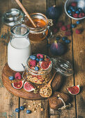 Healthy vegan breakfast, Oatmeal granola with bottled almond milk, honey, fresh fruit and berries on hoard over rustic wooden table background