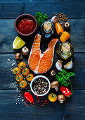 Raw steak of salmon with fresh ingredients for tasty cooking on rustic wooden background