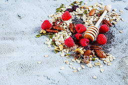 Tasty colorful ingredients for cooking breakfast or smoothie (fresh berries, nuts, oat flakes, dried fruits, chia seeds and honey) over concrete textured background