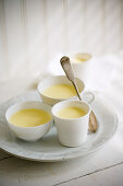 Cups of vanilla pudding on white