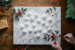 Mexican wedding biscuits with icing sugar on a marble slab