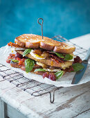 A toasted sandwich with grapes, crispy bacon, camembert and basil