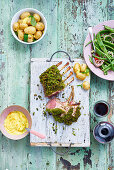 A rack of lamb with a herb crust, potatoes and bean salad