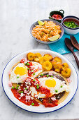 Huevos Motuleños (fried eggs on a tortilla with black bean puree, chilli sauce, plantains, bacon and cheese, Mexico)