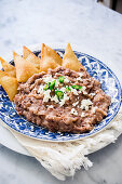 A plate with refried pinto beans garnished with fresh cheese, green chillies and corn fried tortilla (totopos)
