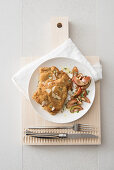 Veal escalopes filled with artichoke and cheese, served with tomato salad