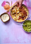 Cheese and ham nachos with guacamole and sour cream