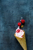 Raspberry ice cream in a cone on a blue grey surface (top view)