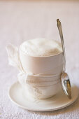 A cappuccino with a bow and a spoon