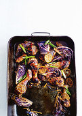 Spicy chicken legs with lime and red cabbage in a roasting dish