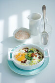 Baked egg with pancetta, sage and onions cream