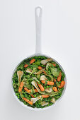 A pan of peas, carrots and spring onions