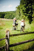 Two girls riding to picnic on bicycles