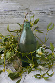 Hot damson water in a green bottle surrounded by mistletoe and a vintage sieve