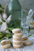 A stack of anise biscuits with shot glasses, a green bottle and an angel figurine in the background