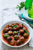 A plate with greek lamb kofta in tomatoe sauce with mint leaves