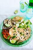 A green plate containing mint marinade grilled chicken, ribboned zucchini salad and grilled vegetables