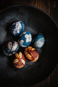 Easter eggs dyed with natural colours and decorated with flowers in a bowl