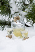 Pear schnapps in two glasses and a carafe in the snow