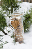 A jar of biscuits decoration with a honey cake heart and a heart-shaped cutter in the snow
