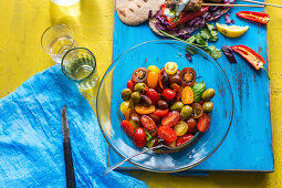 A tomato salad with olives and basil