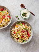 Farfalle salad with tomatoes, peppers, parsley, onion and a yoghurt dressing