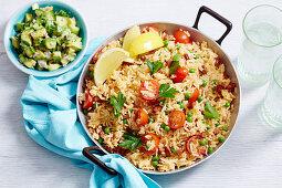 Scharfer Chorizo-Reis mit Tomaten und Erbsen serviert mit Avocadosalsa