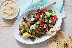 Griechischer Salat mit Lammflleisch serviert mit Dip und Fladenbrot