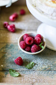 Raspberries on rustic wooden surface with mint