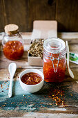 Festive sweet chili sauce in a jar with crackers served as a gift on a rustic wooden surface with a green name tag