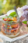 Layered salad with qunioa and vegetables in a jar for a summer picnic