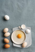 A raw fried egg and eggs on a grey surface