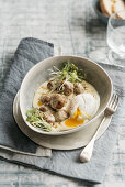 Lamb meatballs with anchovies in a creamy sauce with a poached egg