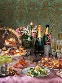 A New Year's Eve buffet with champagne, cheese balls, avocado soup, salmon, hot dogs, toast and flowers