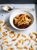 Coconut chips in a marinade made from soy sauce, maple syrup, smoked pepper, smoked salt and oil