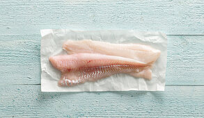 Light cod fillets on a piece of paper
