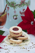 Jam sandwich biscuits, mulled wine, a tin and a poinsettia