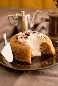 Coffee and cinnamon savarin with whipped cream and chocolate sprinkles