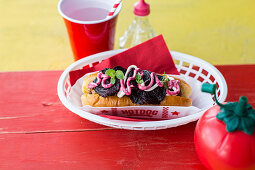 Hot Dog with pork sausage with beetroot crisps, mint and beetroot sauce