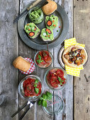 Pea hummus, puff pastry with carrots, and baked tomatoes on a rustic wooden table